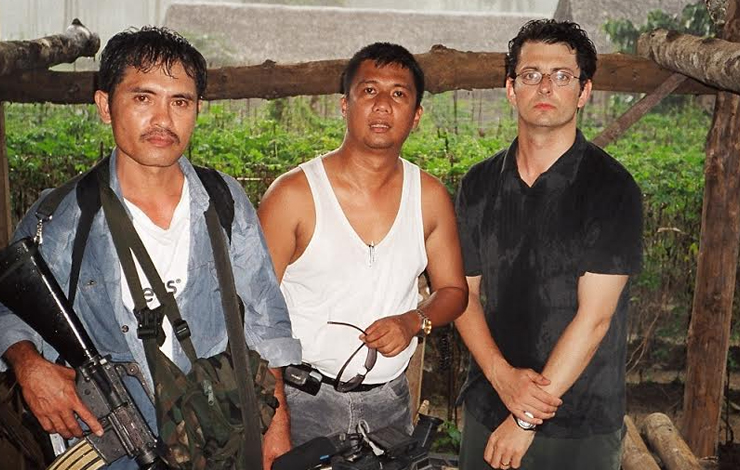 An armed guard (left) protects journalist Herman P. de la Cruz (center), editor of the 'Zamboanga Scribe,' with CameraPlanet producer Jack Youngelston by his side. Courtesy of CameraPlanet