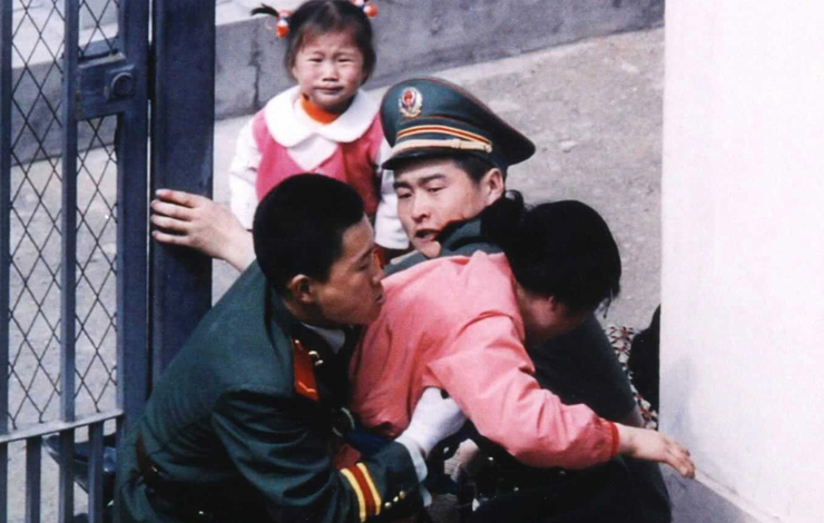 Two-year-old Kim Han-mi looks on in agony as her mother is wrestled to the ground by Chinese guards at the Japanese consulate in Shenyang, China. From 'Seoul Train.' Courtesy of Incite Productions