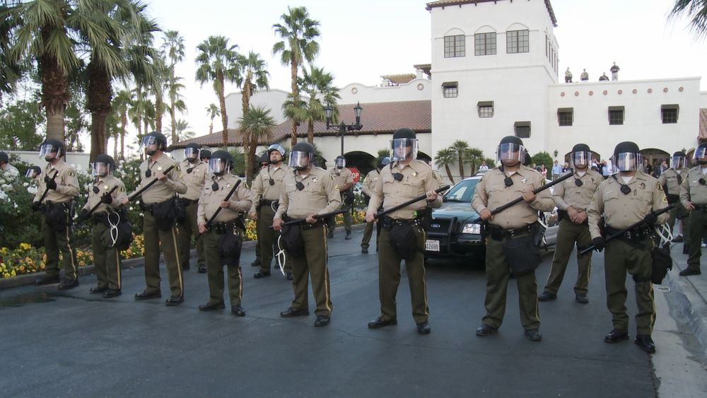 Police guarding a conservative fundraisier and poltical strategy meeting attend by the Koch brothers. Courtesy of Variance Films/Elsewhere Films