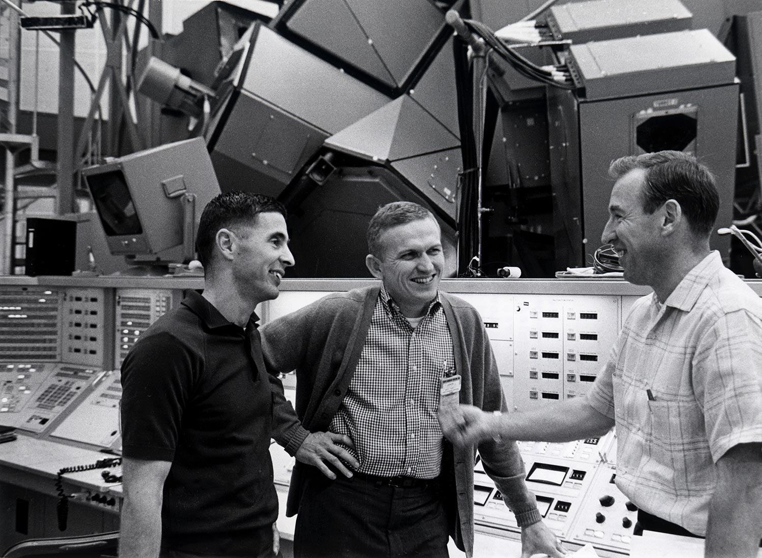 Apollo 8 crew members paused before the mission simulator during training for the first manned lunar orbit mission. Frank Borman, Commander (center); James Lovell, Command Module Pilot (right); and William Anders, Lunar Module Pilot (left). December 17, 1968.. From Robert Stone's 'Chasing the Moon.' Courtesy of American Experience