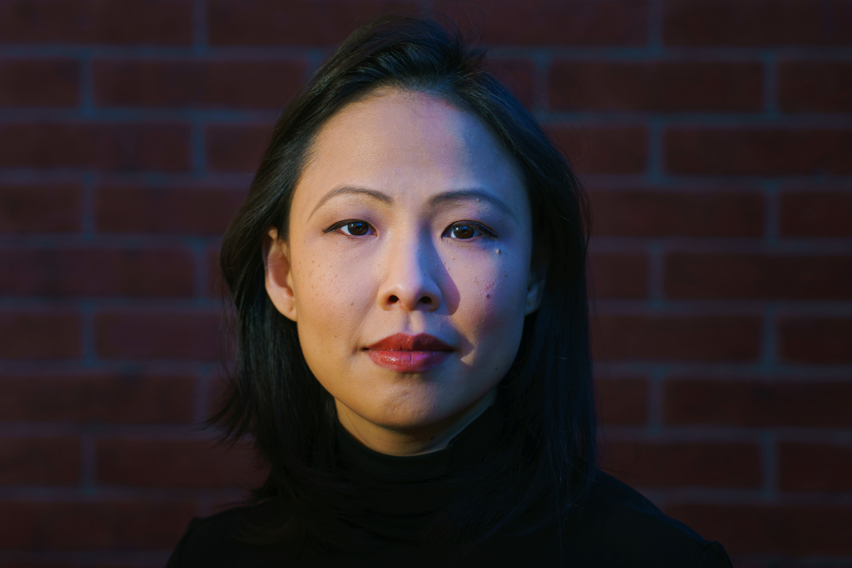 Poh Si Teng is an Asian woman of Malaysian Chinese origin with shoulder-length black hair. She is wearing a black turtleneck & in front of a brick wall. Photo by Marcus Yam