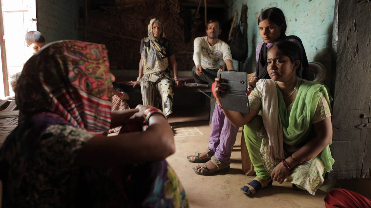 From Rintu Thomas and Sushmit Ghosh's 'Writing with Fire.' Courtesy of Sundance Institute. At right, A reporter from an India-based digital platform is kneeling while interviewing an Indian woman who is seated at left, in her living space with her family. The reporter is filming with a smartphone in her right hand , nd is wearing an emerald green sari