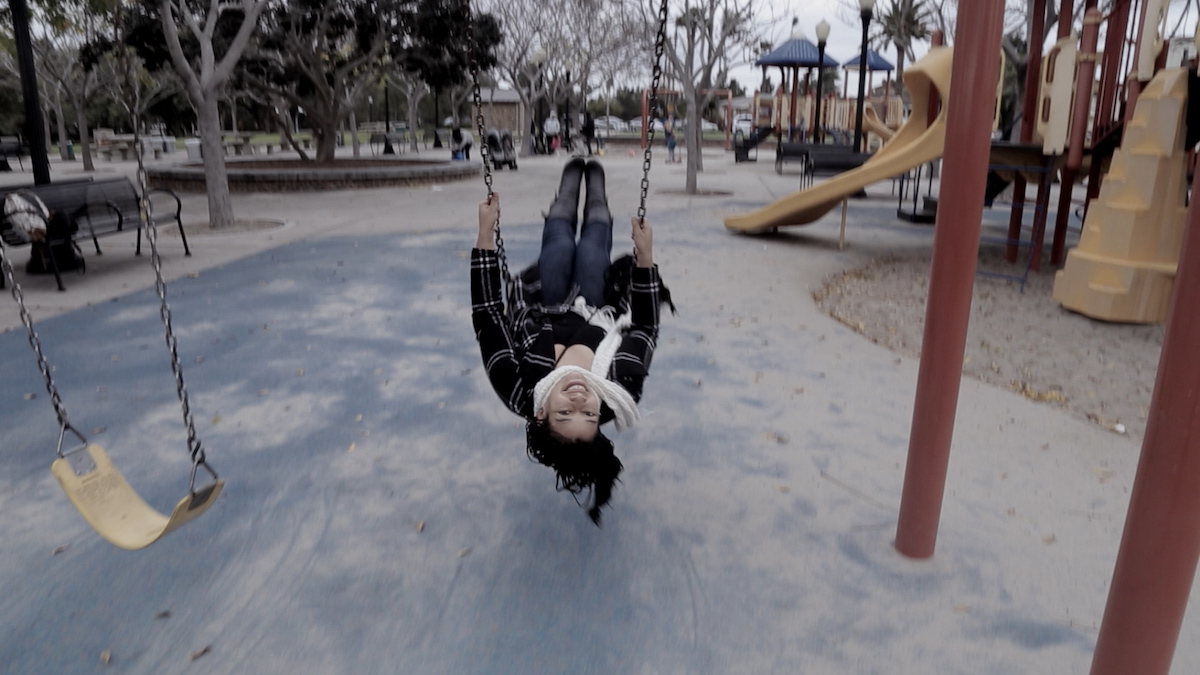 From Olga 'Busy Inside.' Courtesy of WORLD Channel. A woman from the film swings on  a swing in the middle of a playground; her head is upside-down as she faces the camera.