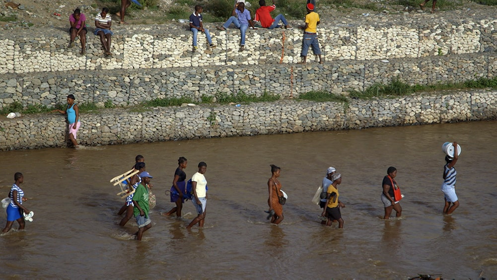 A group of people walking through a shallow river at the border between Haiti and the Dominican Republic. From Michele Stephenson's 'Stateless.' Courtesy of National Film Board of Canada.