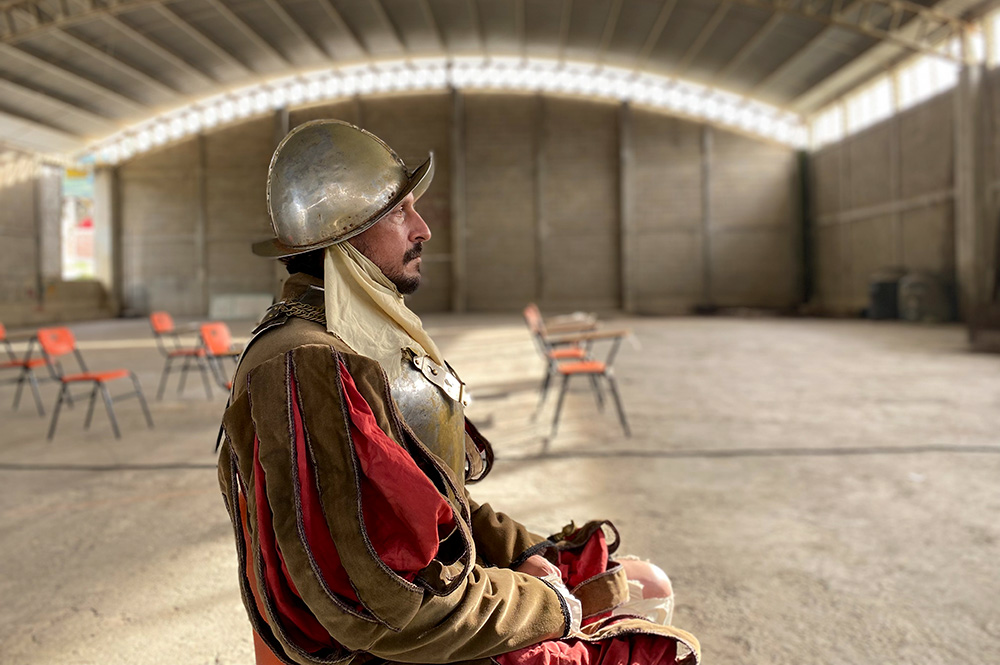 """Actor Eduardo San Juan Breña is a bearded Mexican man dressed as a Conquistador. He has a metallic helmet and armor, and is wearing a red and brown costume. Image from Rodrigo Reyes' """"499."""" Courtesy of the filmmaker."""