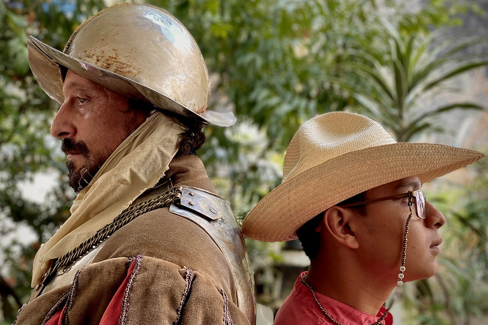 """Actor Eduardo San Juan Breña is a Mexican man with a beard, dressed as the Conquistador. He is standing next to musician Tomás de Aquino, who is wearing a red shirt, a straw hat and glasses, with a beaded suspender. Image from Rodrigo Reyes' """"499."""" Courtesy of the filmmaker."""