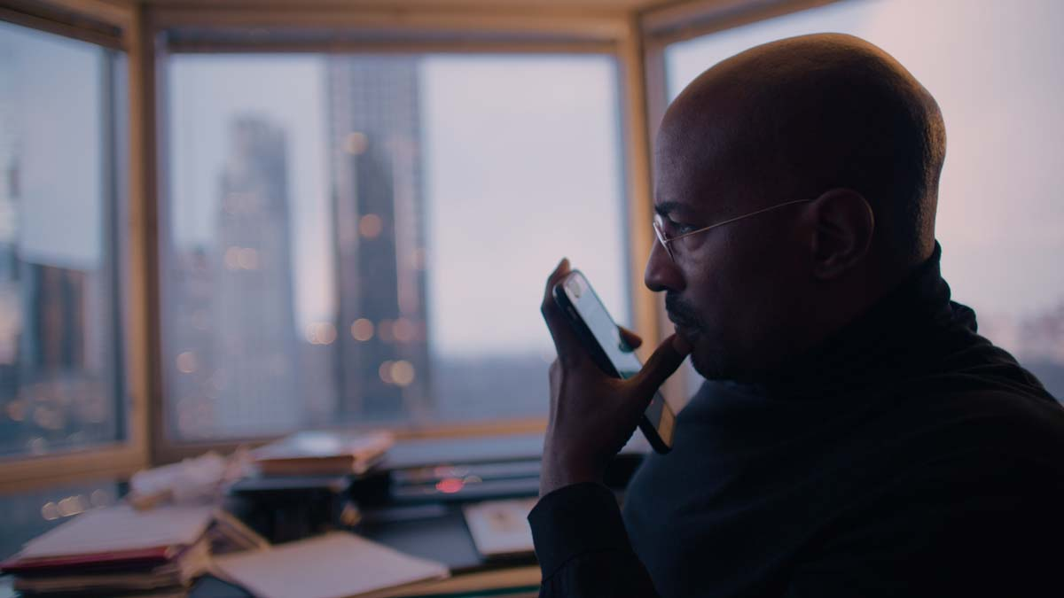 Side profile of Van Jones, a bald Black man holding a cellphone, wearing glasses. From Brandon and Lance Kramer's 'The First Step.' Courtesy of AFI Docs.