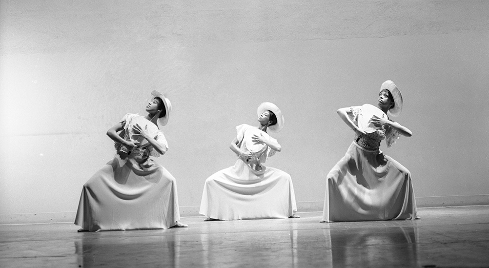 Black-and-white image of three Black women dancers holding a pose wearing long dresses, hats, paper fans in their hands. Image from Jamila Wignot's 'Ailey.' Courtesy of NEON.