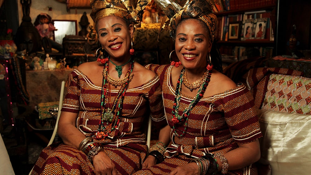 The Lijadu Sisters are a Nigerian singing duo. Taiwo and Kehinde Lijadu are two Black women wearing their traditional dress with jewelry and shiny black and golden headwraps. Image from Siji Awoyinka's 'Elder's Corner: A Musical Voyage of Discovery'. Courtesy of BlackStar Film Festival.