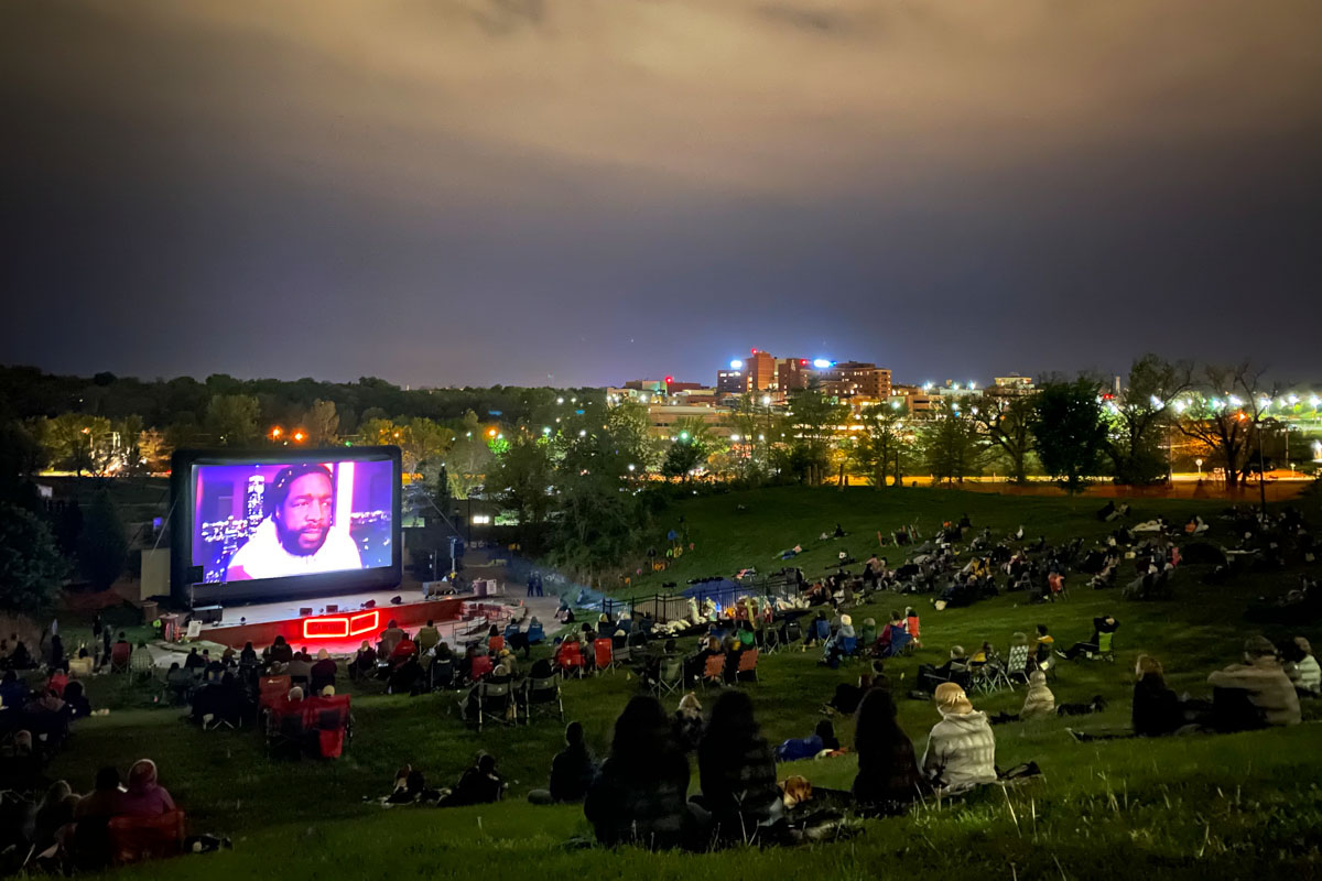 """An outdoor screening of 'Summer of Soul' at True/False 21. It is night time and people are sitting on chairs and on grass. The projector screen shows the film's director, Ahmir """"Questlove"""" Thompson, who is a Black man with a beard and short black hair. Courtesy of True/False"""