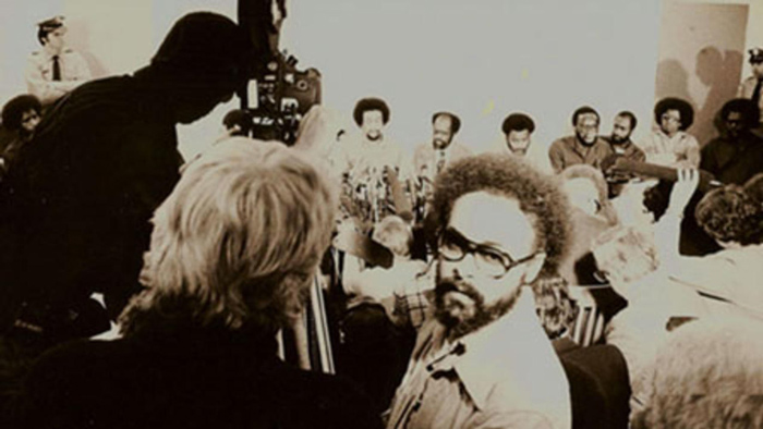 Haile Gerima is a Black filmmaker with short curly hair and a beard. He is seen filming 'Wilmington 10, U.S.A – 10,000' (1979). Image courtesy of The Academy Museum of Motion Pictures.