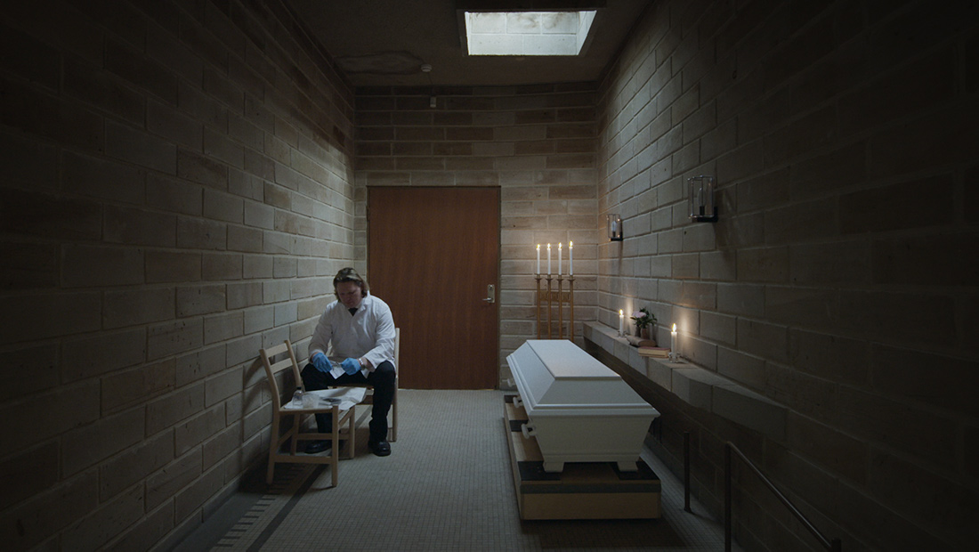 A funerary worker sitting on a chair, next to a closed coffin. There are lit candles surrounding him. A still from 'Meanwhile on Earth,' directed by Carl Olsson. Courtesy of Syndicado Film Sales.
