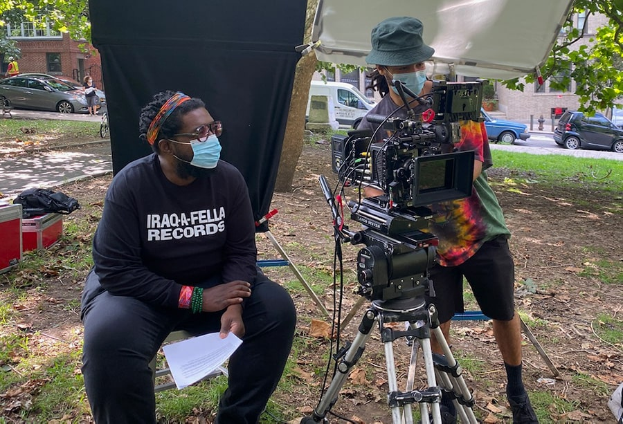 """Filmmaker Ahmir """"Questlove"""" Thompson, a Black man in a colorful headband and black tshirt sitting, and DP Shawn Peters, a Black cameraperson with a green hat, on the sets of """"Summer of Soul."""" Courtesy of Searchlight Pictures."""