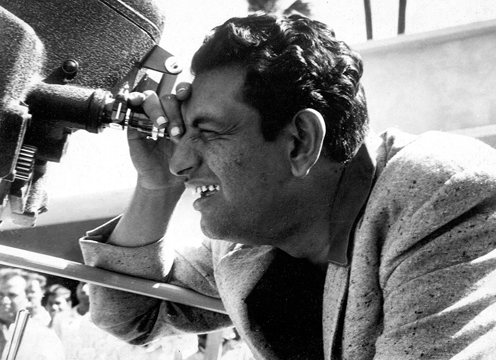 Black and white photo of Satyajit Ray looking through a camera. Courtesy Criterion Channel.