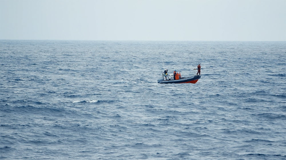 A long-lens shot of the RHIB, an orange-and-grey inflatable boat, amidst a blue sea from the research vessel. Courtesy of Bleecker Street.