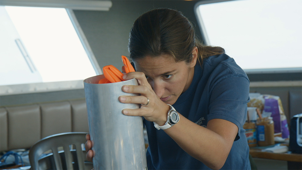 A white female marine biologist in a blue shirt holding the grey tube of a sonabuoy. Courtesy of Bleecker Street.