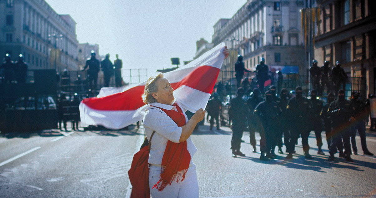 A white woman in a white shirt and pants and a red shawl carries a red and white flag across a city street. From Aliaksei Paluyan's 'Courage.' Courtesy of CPH:DOX