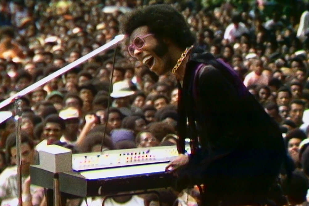 Sly Stone, a Black male musician in a velvet coat singing to a large audience at the Harlem Cultural Festival. Courtesy of Searchlight Pictures.
