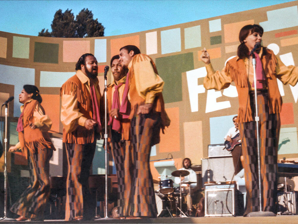 The 5th Dimension, Five singers, two women and three men, in orange and brown outfits singing on a stage, at the Harlem Cultural Festival. Courtesy of Searchlight Pictures.