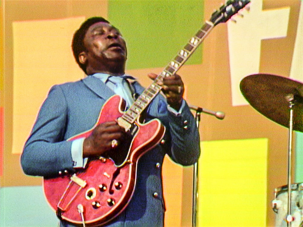 BB King, a Black man in a grey suit playing a red guitar, at the Harlem Cultural Festival. Courtesy of Searchlight Pictures.
