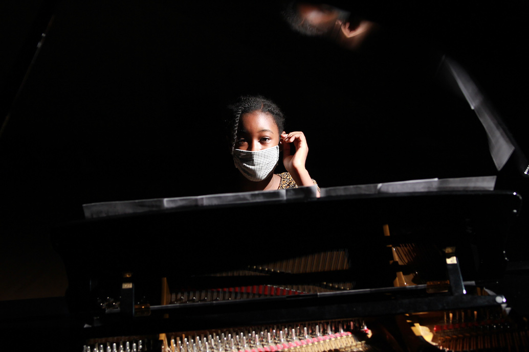 Grace Moore is a Black teenager with braided hair. She is wearing a mask and is sitting at a piano. Image from Arielle Knight's 'Song of Grace.' Courtesy of Tribeca Festival