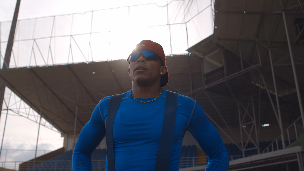 Happy Oliveros is an Afro-Latino man in a blue t-shirt with suspenders. He is wearing sunglasses and a red hat. Image from Sami Khan and Michael Gasset's 'The Last Out.' Courtesy of Tribeca Festival