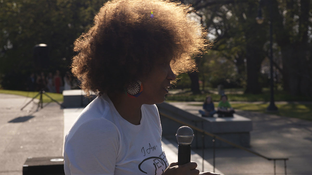 Vivian Anderson, a Black woman with short, brown curly hair and wearing a white shirt,  addresses a crowd at the South Carolina State House . From Garrett Zevgetis' 'On These Grounds.'