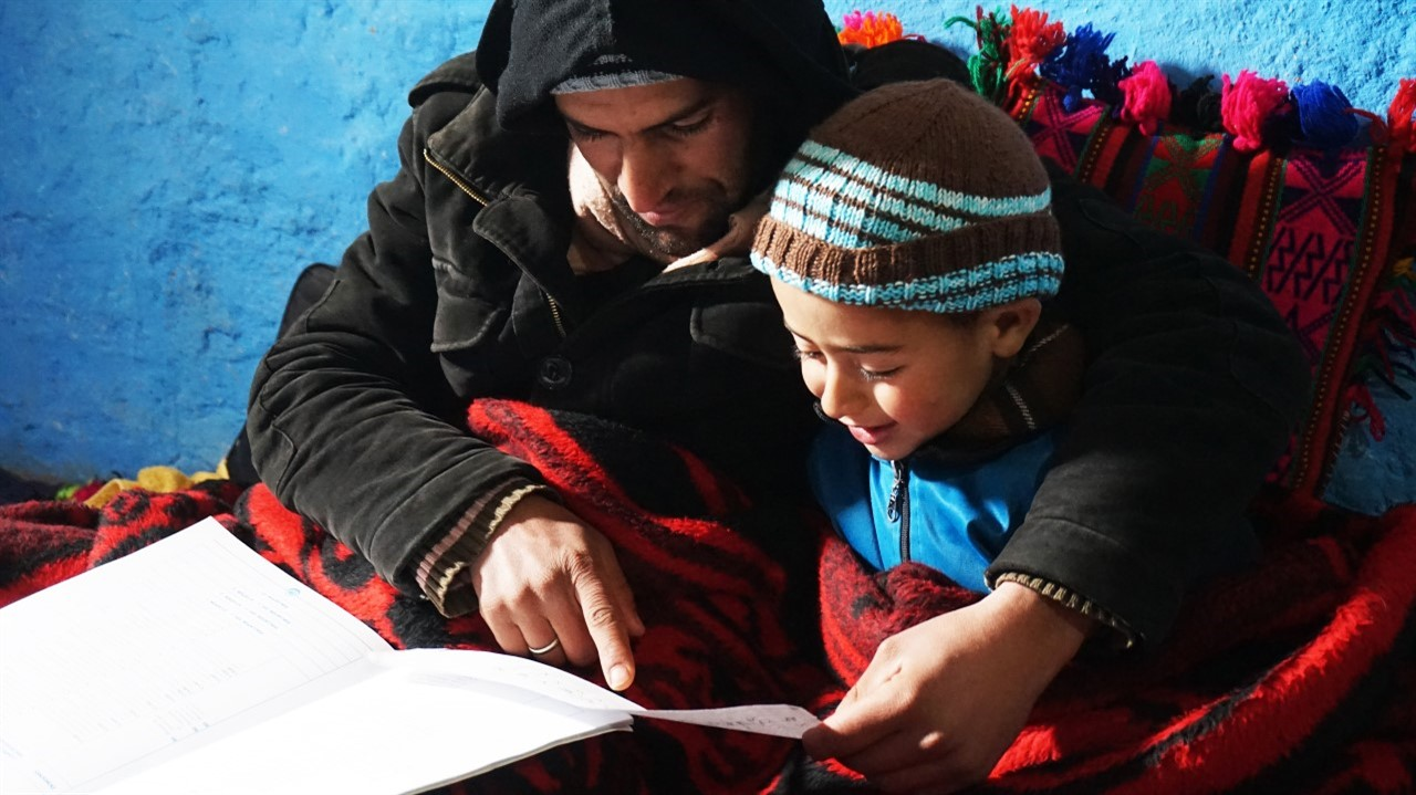 An Indigenous Moroccan helps his child with his school lesson. Both are wearing warm winter clothing. From Mohamed El Boudi's 'School of Hope', courtesy of Hot Docs.
