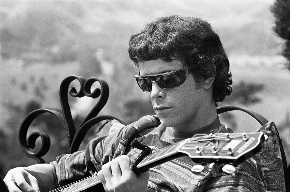 Lou Reed, a white male with black wraparound shades and black hair and a striped shirt, sits on a bench playing a guitar. From Todd Haynes' 'The Velvet Underground.' Courtesy of Apple TV.