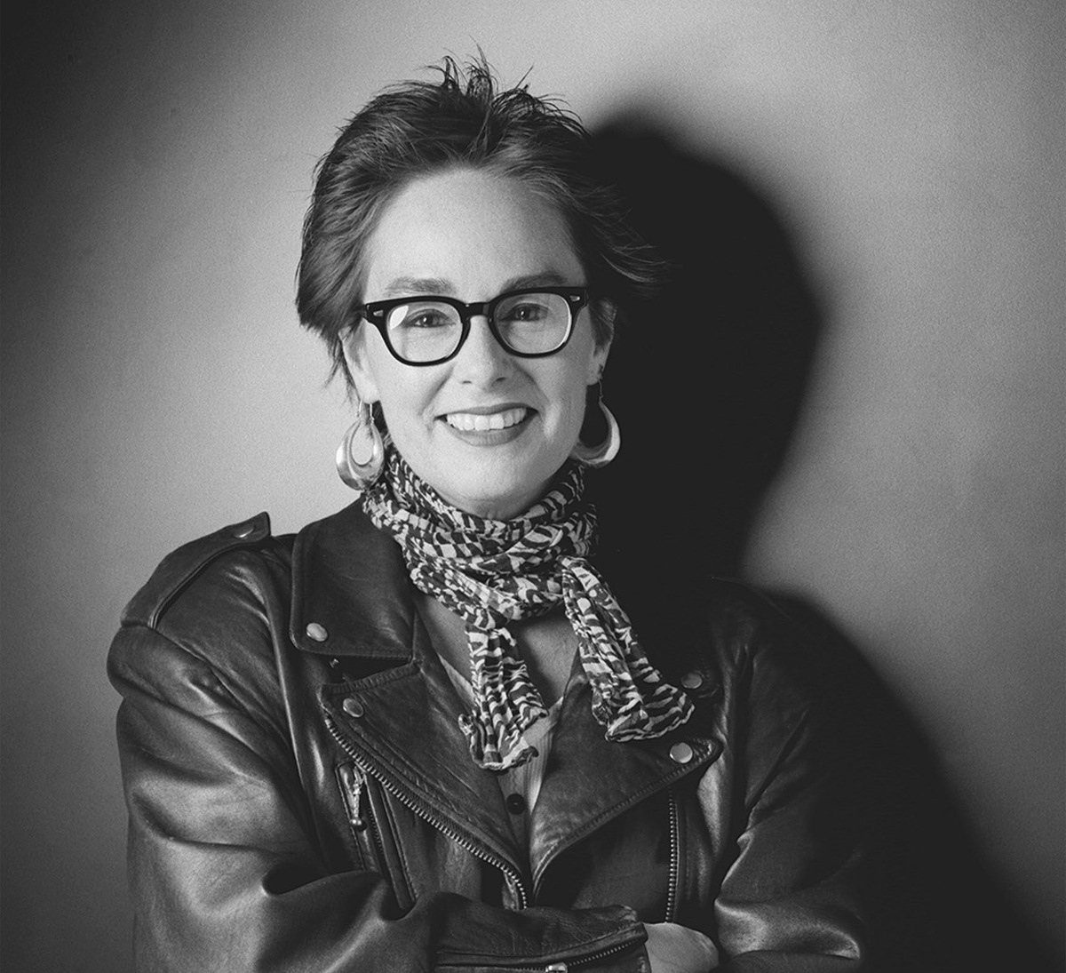 The late filmmaker/educator Judy Irola. Photo: Douglas Kirkland. Courtesy of American Society of Cinematographers. In this black-and-white portrait of Judy Irola, she has short brunette hair and glasses, she is wearing a leather jacket and she is posing with her arms crossed across her chest.
