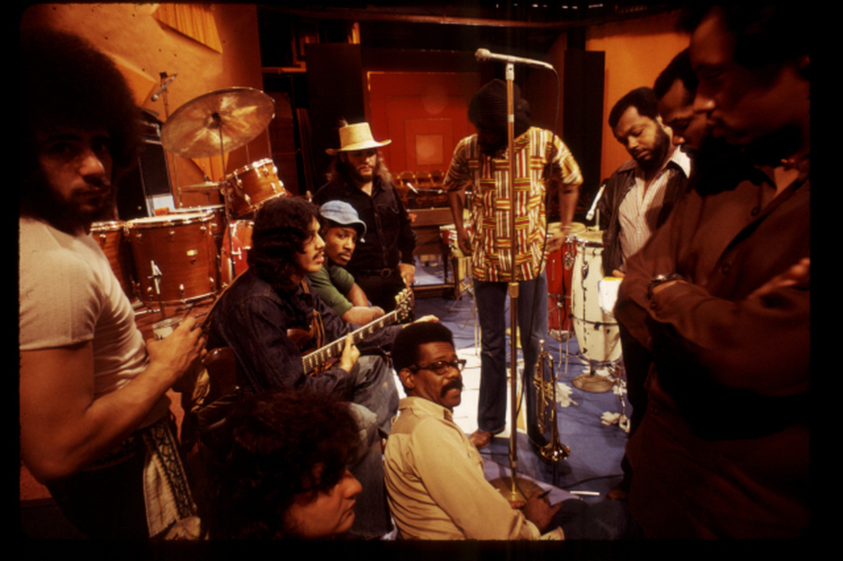 From Melissa Haizlip's 'Mr. SOUL!' Courtesy of Alex Harsley. The subject of the documentary, Ellis Haizlip, sits in the middle of the set of his variety show 'SOUL' surrounded by members of the '70s funk band Mandrill, some members of whom are holding their instruments.