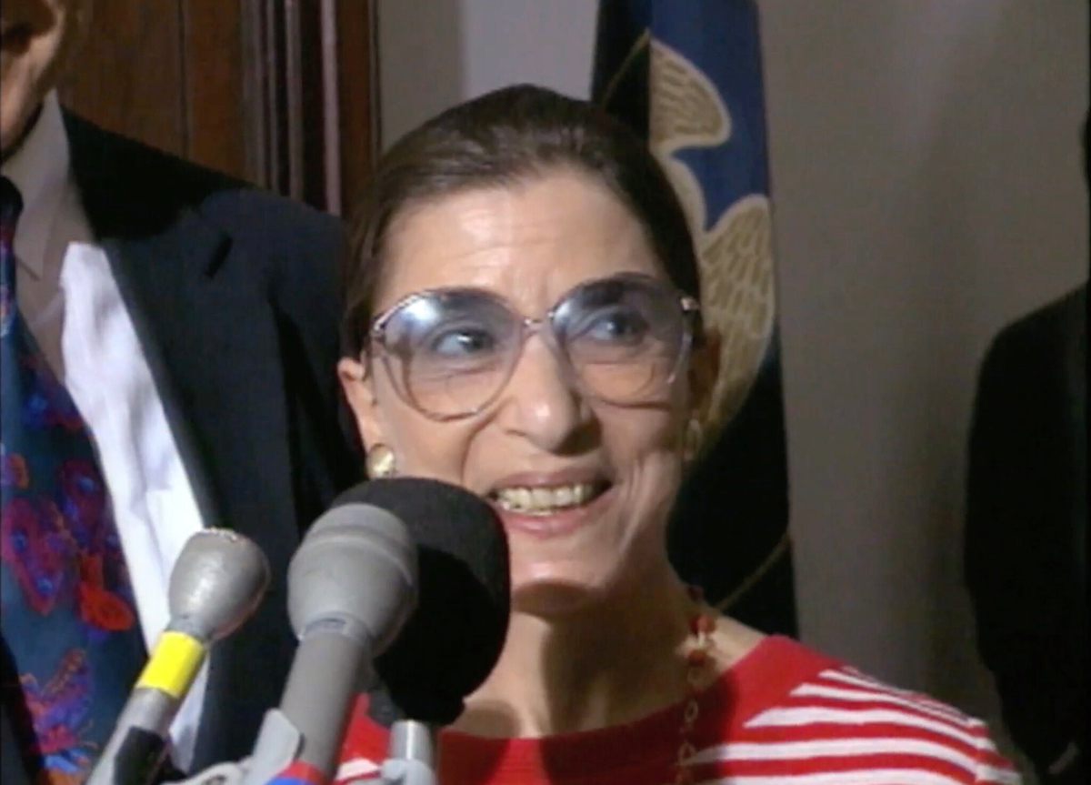 The late Supreme Court Justice Ruth Bader Ginsburg, subject of Freida Lee Mock's 'RUTH--Justice Ginsburg in Her Own Words.' Courtesy of Starz. Justice Ginsburg is pictured here at a press conference, in front of a bank of microphones, and she is wearing a red-and-white striped shirt.