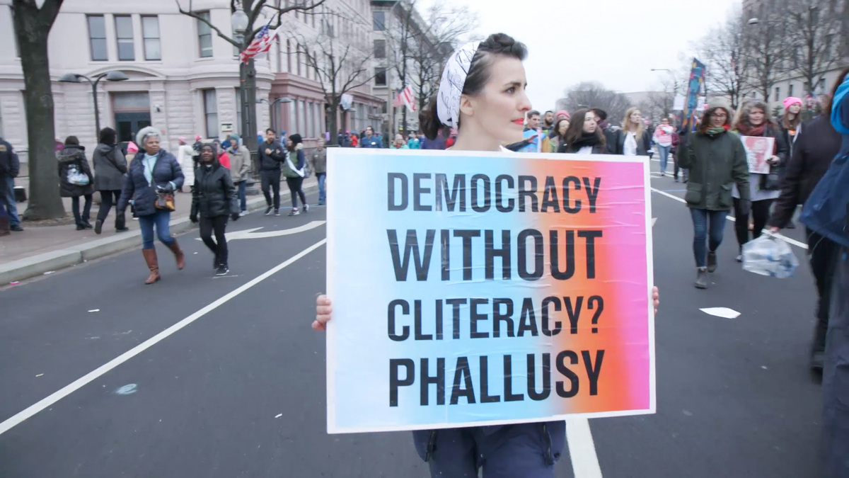 """From Maria Finitzo's 'The Dilemma of Desire.' In this image, a woman is particpating in a demonstration on a city street; she carries a sign that reads """"Democracy without cliteracy? Phallusy."""" Courtesy of Kartemquin Films"""