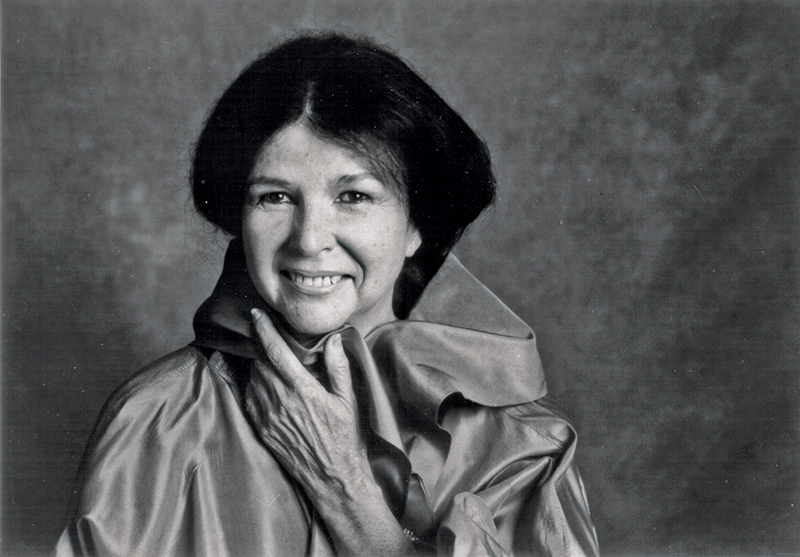 Black & white photo of a middle-aged Alanis Obomsawin. She has dark straightened hair and is wearing a satin cape.