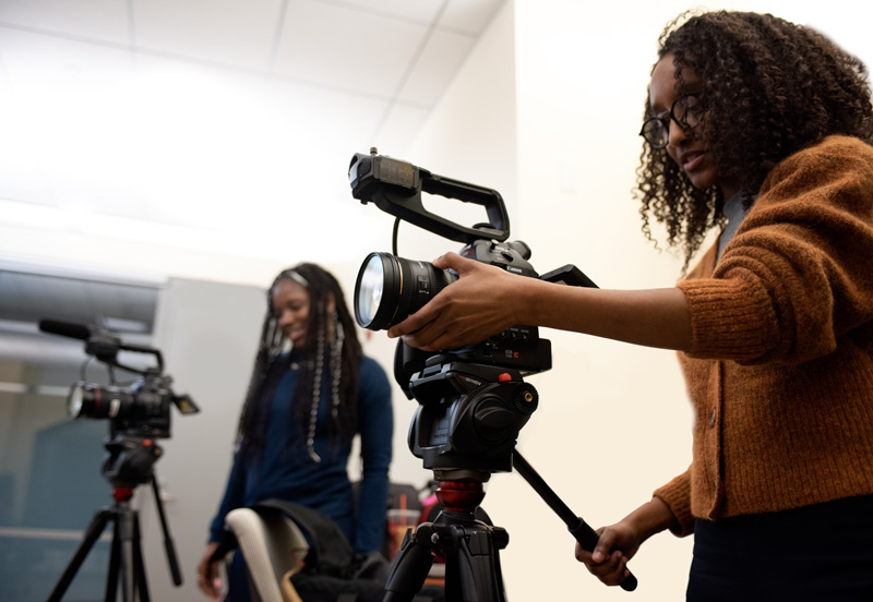 Two students at CUNY's Newmark Journalism School are looking into video cameras. Credit: Marco Poggio