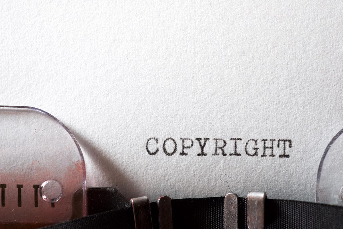 """Word """"Copyright"""" written on a sheet of paper in a type-writer."""