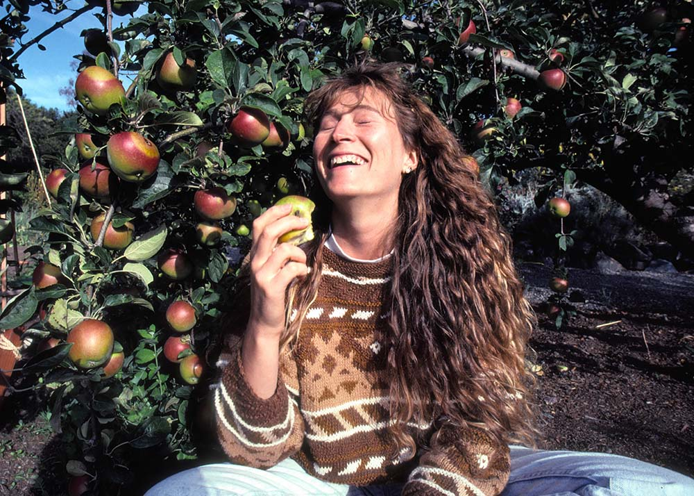 Image of a smiling white woman in a brown sweater with long hair, sitting under an apple tree. From Mark Kitchell's 2017 film 'Evolution of Organic.' Courtesy of Mark Kitchell.