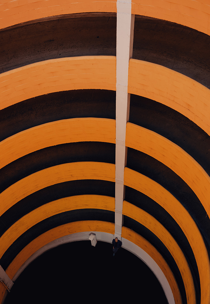 Photo by Adam G Perez. Photo taken from the top of circular parking ramp that is painted in a gradient orange.