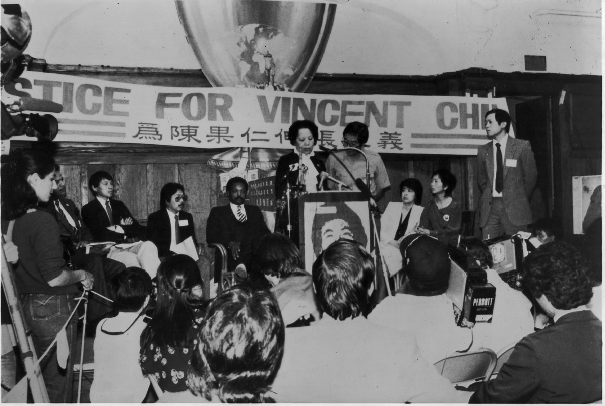 """From Renee Tajima-Pena and Chritine Choy's 'Who Killed Vincent Chin?' Courtesy of Renee Tajima-Pena. The photo captures a rally for justice for Vincent Chin, who was murdered in 1982 in Detroit in an anti Asian hate crime. At podium ois Vincent Chin's mother; seating behind her are several activists from the Asian American community, as well as civil rights leader Jesse Jackson. A banner above them states """"Justice for Vincent Chin."""""""