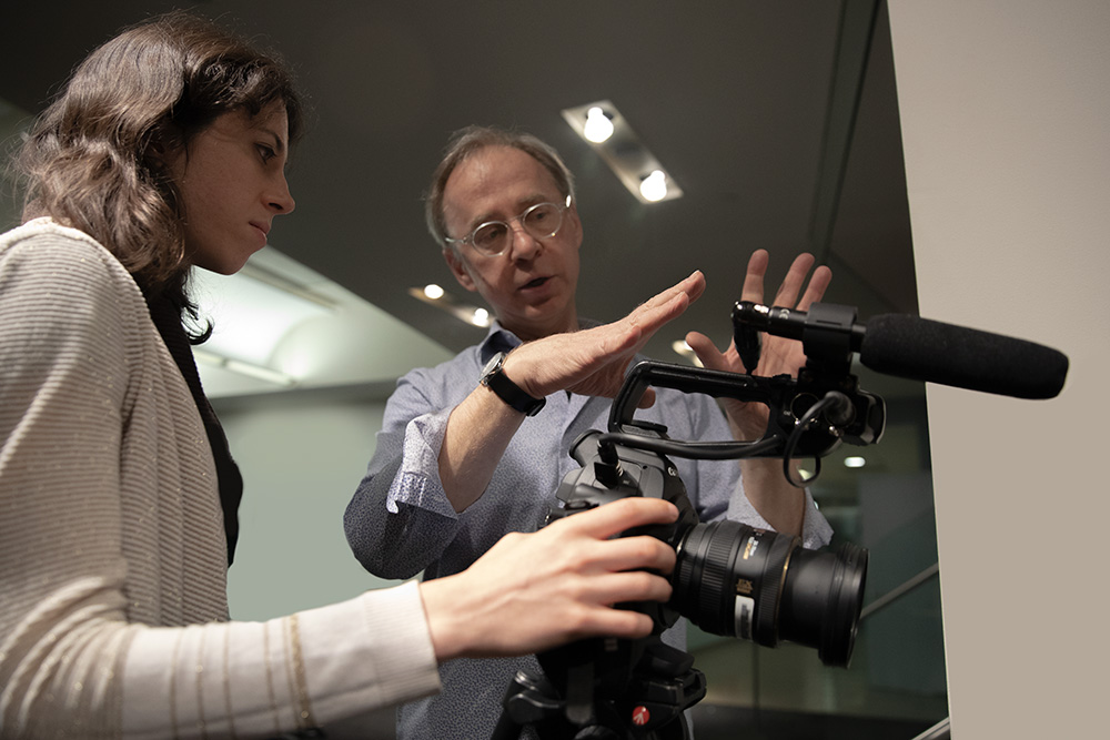 Bob Sacha, a white male professor, working with a young female student at Newmark J School. Both of them are looking at a camera fitted with a microphone. Photo by Marco Poggio.