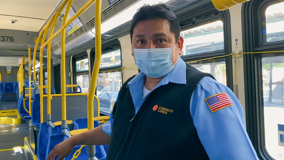 Arlet Guillpa's fatrher, Carlos Guillpa, at his job as a bus driver in New York City. He is wearing his work uniform, as well as a protective mask, and he is standing in his bus. From 'COVID Diaries NYC.' Courtesy of HBO