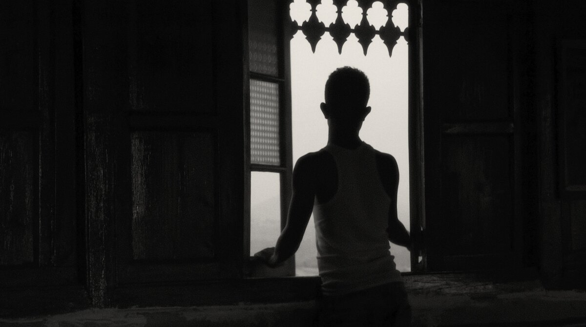 A silhouette of Mohammed Arif standing in front of a window with patterned glass and an ornate frame. Image from Jessica Beshir's 'Faya Dayi.' Courtesy of Cinetic Media.