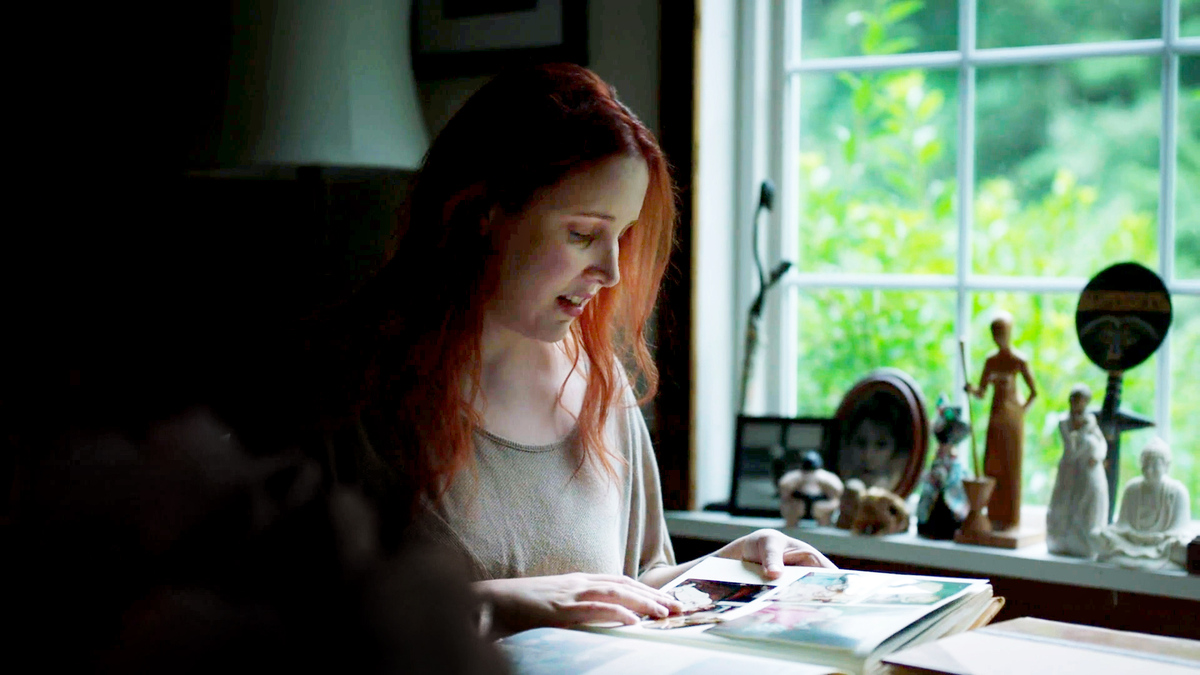 Dylan Farrow, featured in Kirby Dick and Amy Ziering's 'Allen Vs. Farrow.' Dylan is a white woman, with red hair, in her early 30s; she is sitting at a desk next to a window, and she is looking at a photo album. Courtesy of WarnerMedia