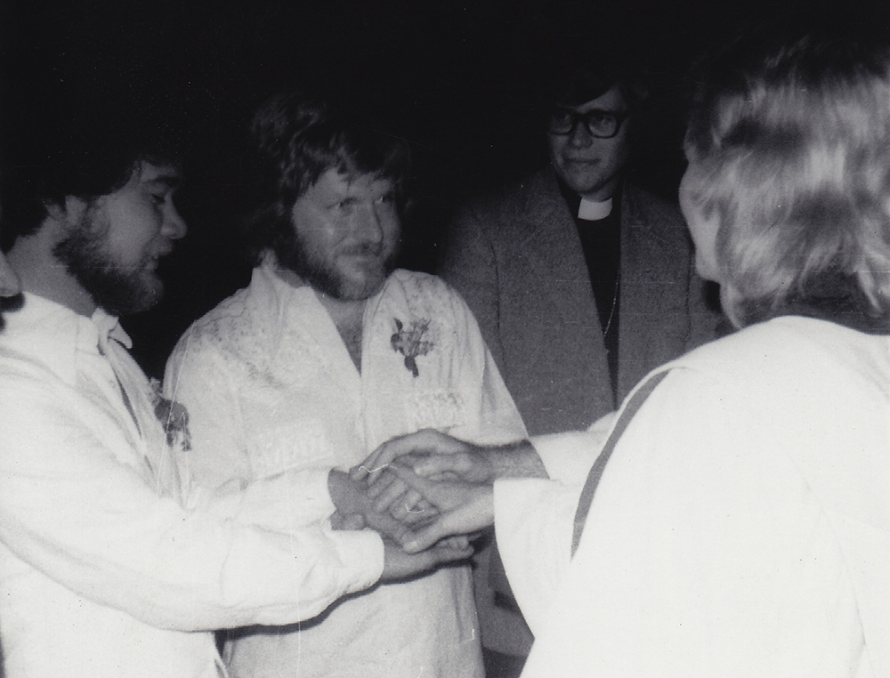 Reverend Frieda Smith marries Richard Adams (L) and Tony Sullivan (R) as Charles Arehardt looks on. Boulder, CO. April 21, 1975. Photo by Ron Wilson