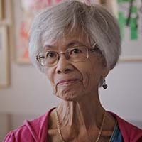 An older woman with gray hair and round glasses.