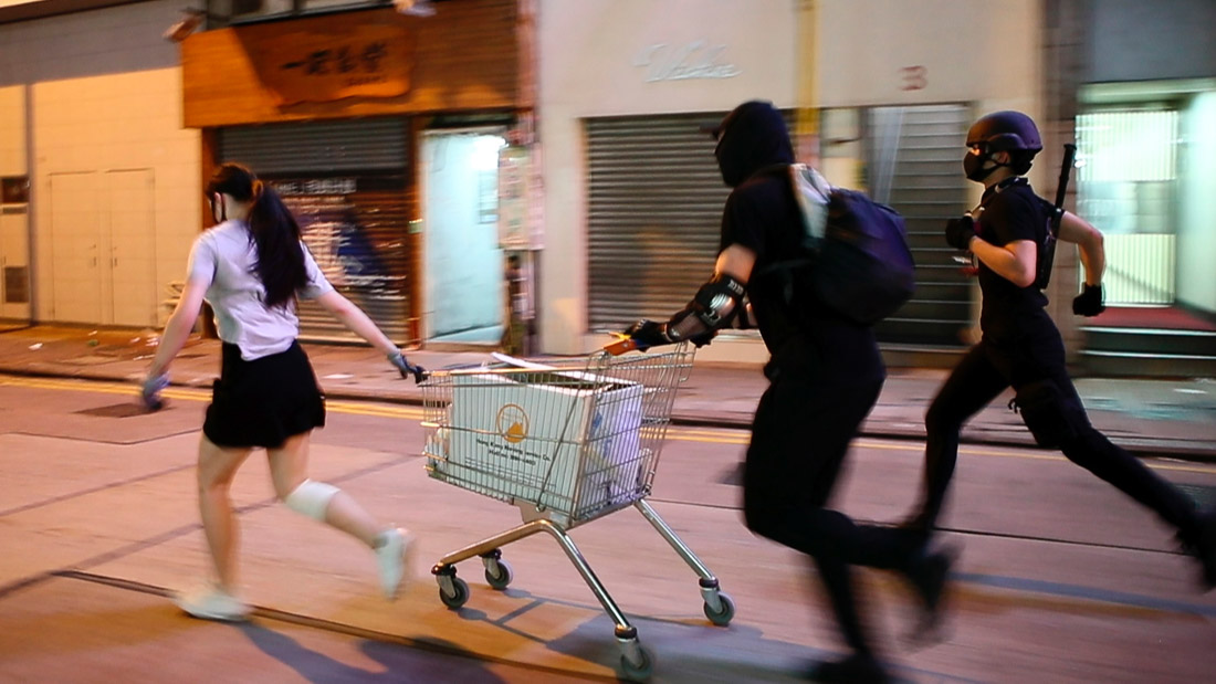 A still from 'Do Not Split', nominated for Best Documentary Short at the 93rd Academy Awards. The frame shows three young protestors in Hong Kong running down an empty street with a shopping cart.