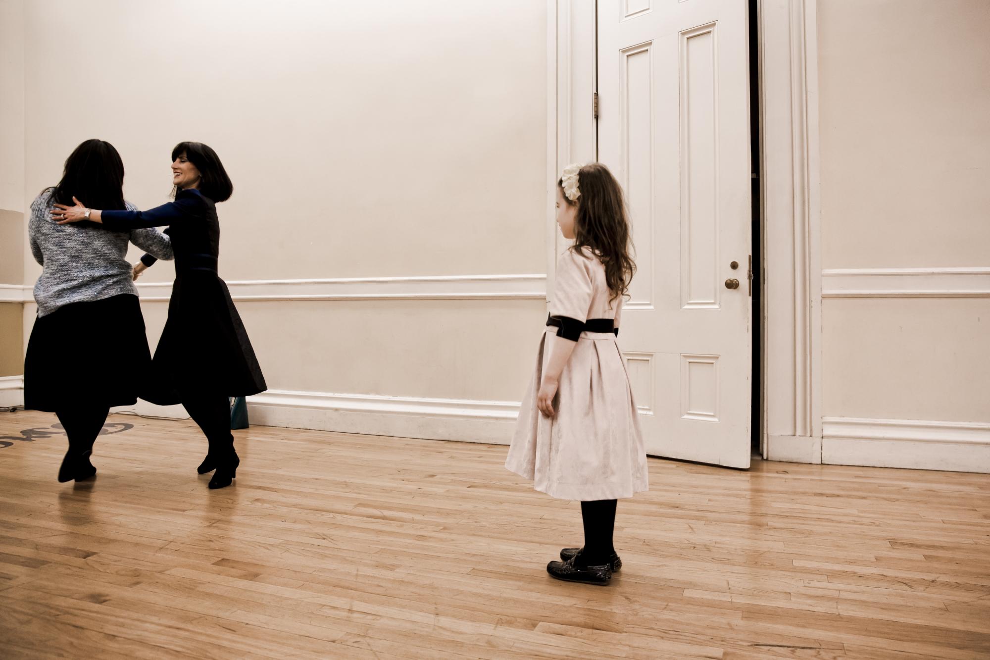 """Ruchie Freier's granddaughter looks on as her grandmother, Rachel """"Ruchie"""" Freier (center) dances with Ruchie's sister, Chavie. Courtesy of Paula Eiselt and Heidi Reinberg"""