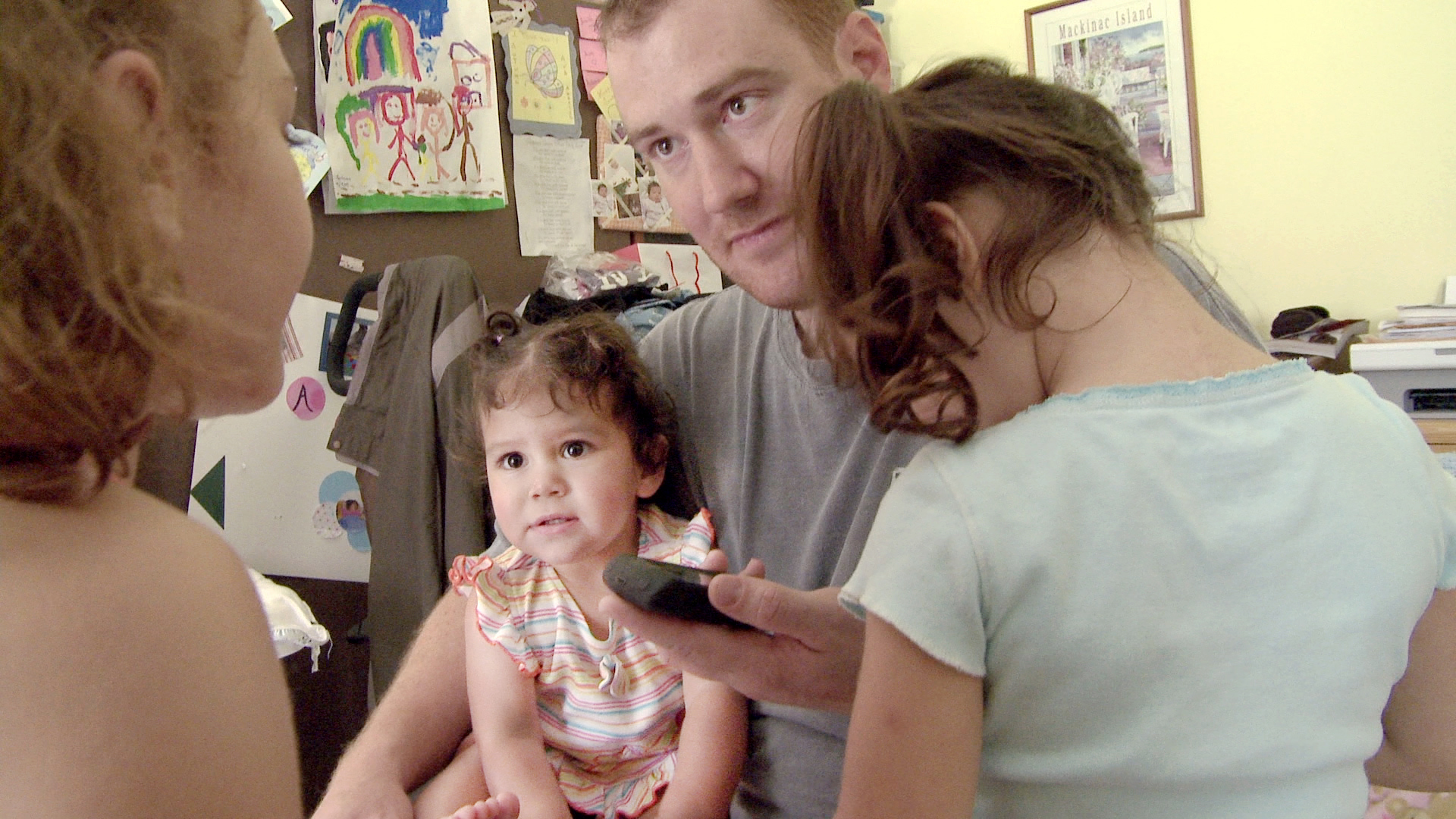 Cindy Shank's then-husband, Adam, with their kids, talking to Cindy on the phone. Courtesy of HBO