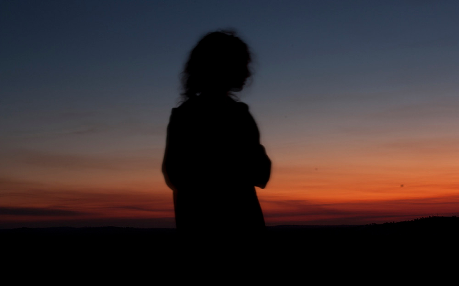 Stock image of woman looking onto the sunset.