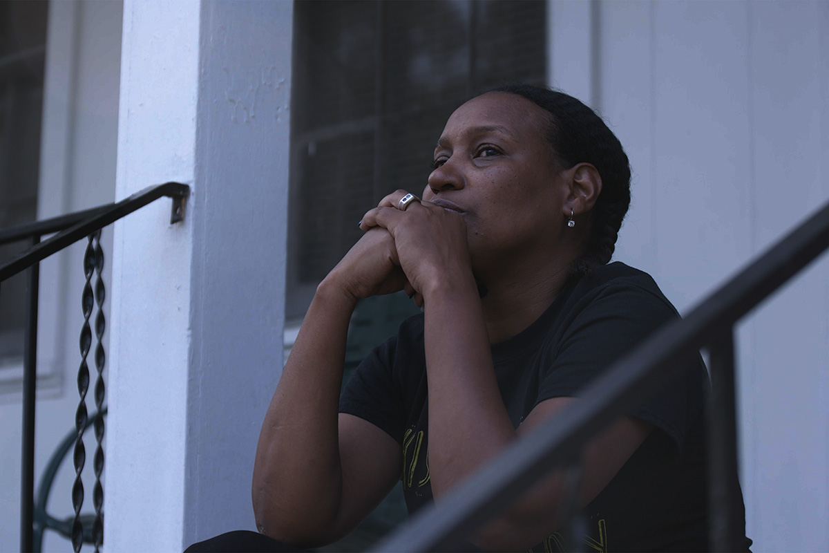 Vivian Anderson is a Black woman sitting on a stoop, with her hands folded against her chin. From Garrett Zevgetis' 'On These Grounds.'